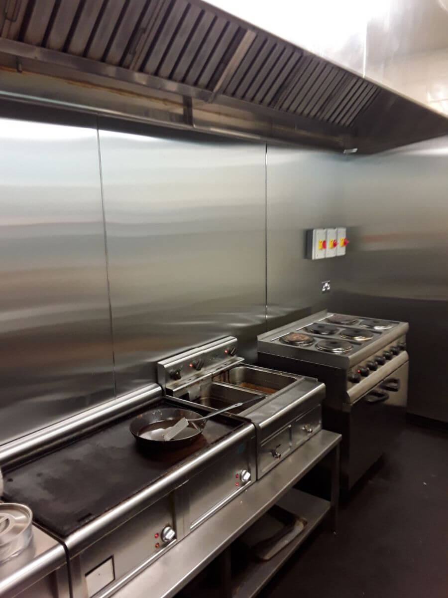 Inside a busy cafe kitchen, stainless steel walls and canopy