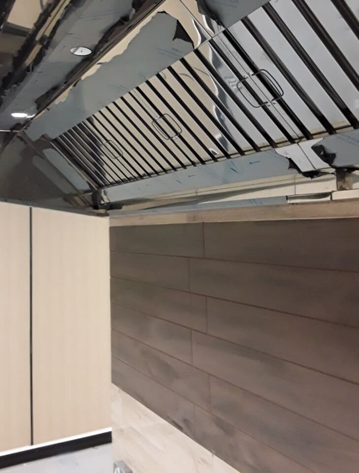 Stainless steel canopy above marl grey tiles